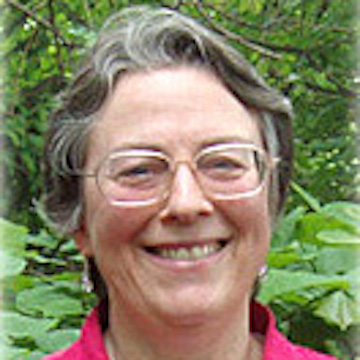 A portrait of a woman with grey hair and glasses