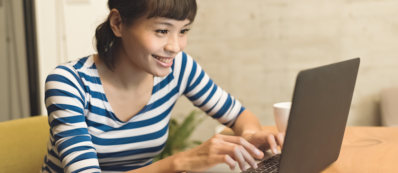An asian woman wearing a stripped shirt smiling and typing on her computer. Take online classes at Hawthorn.