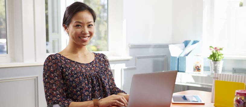 An asian woman working on a laptop in her home. Take an Online Nutrition Consultant Certificate at Hawthorn.