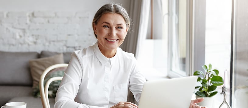 A woman with grey hair, wearing a white shirt, in an open and naturally lit space. Take your Doctor of Science in Holistic Nutrition degree at Hawthorn.