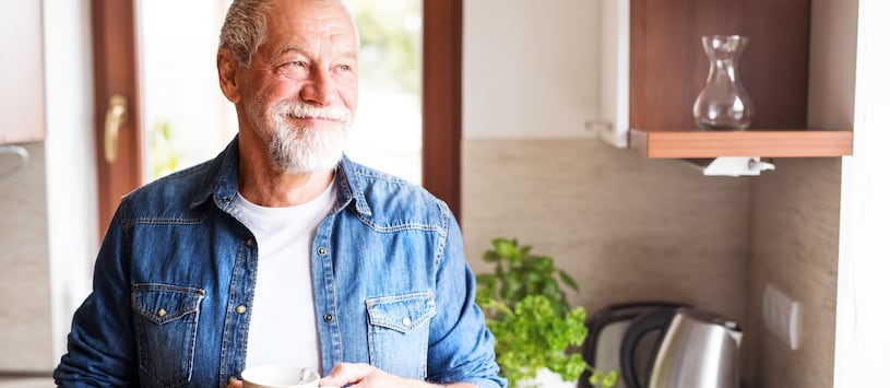 An older man in his kitchen gazing out of the window with a basil plant in the background. Take an online Wise Traditions Nutrition Certificate from Hawthorn.