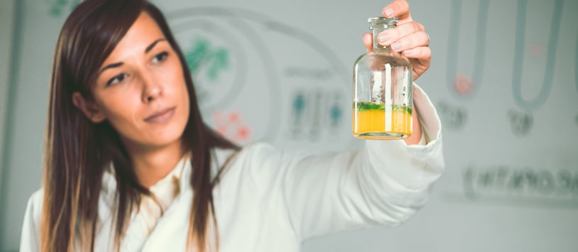 A woman wearing a lab coat and holding up a glass jar with herbs in it. Take the Master of Science in Traditional Nutrition degree at Hawthorn.