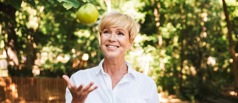 A woman with short blonde hair throwing a green apple in the air. Start your Master of Science in Holistic Nutrition Degree at Hawthorn.