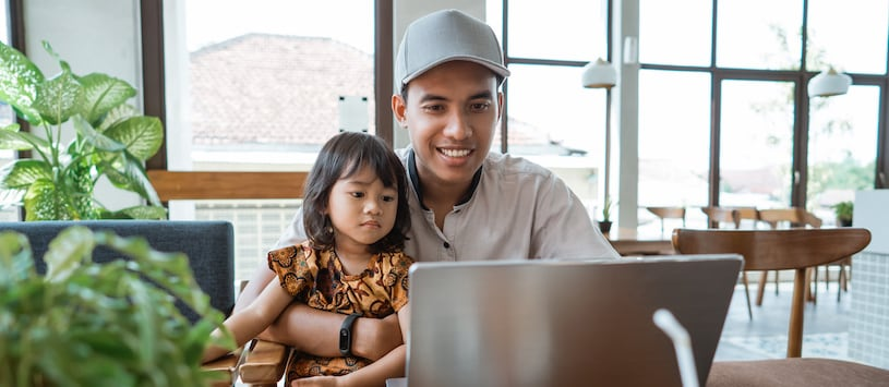 A man holds his toddler daughter while on his laptop at a cafe. Sign up for Continuing Education classes at Hawthorn.